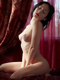 Naked black haired girl posing in her bedroom