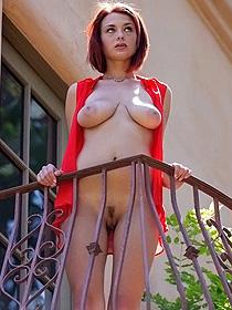 Busty Redhead Posing On The Balcony