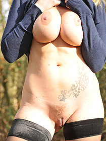 Busty MILF Posing In The Forest